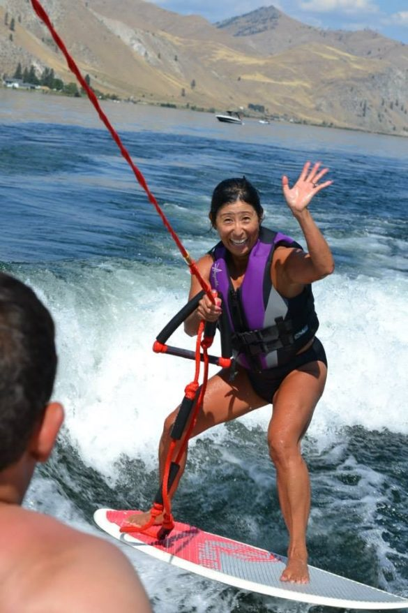 Woman smiling and waving to the camera while wakeboarding in a lake