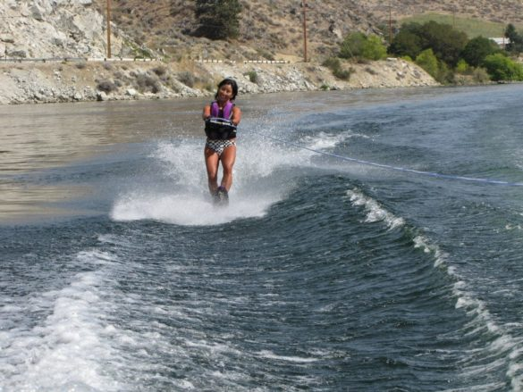 Woman smiling while water-skiing in a lake alone