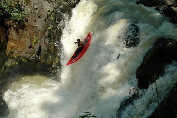 A person kayaking in a rapid river alone