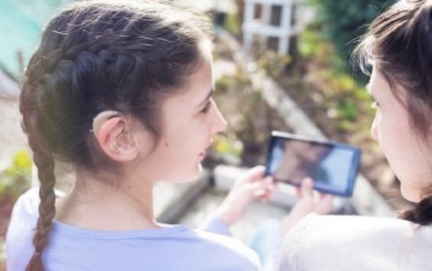 Picture of two girls. One is holding a phone and wearing a hearing aid