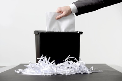 Picture of hand putting paper into paper shredder with shreddings at the bottom.