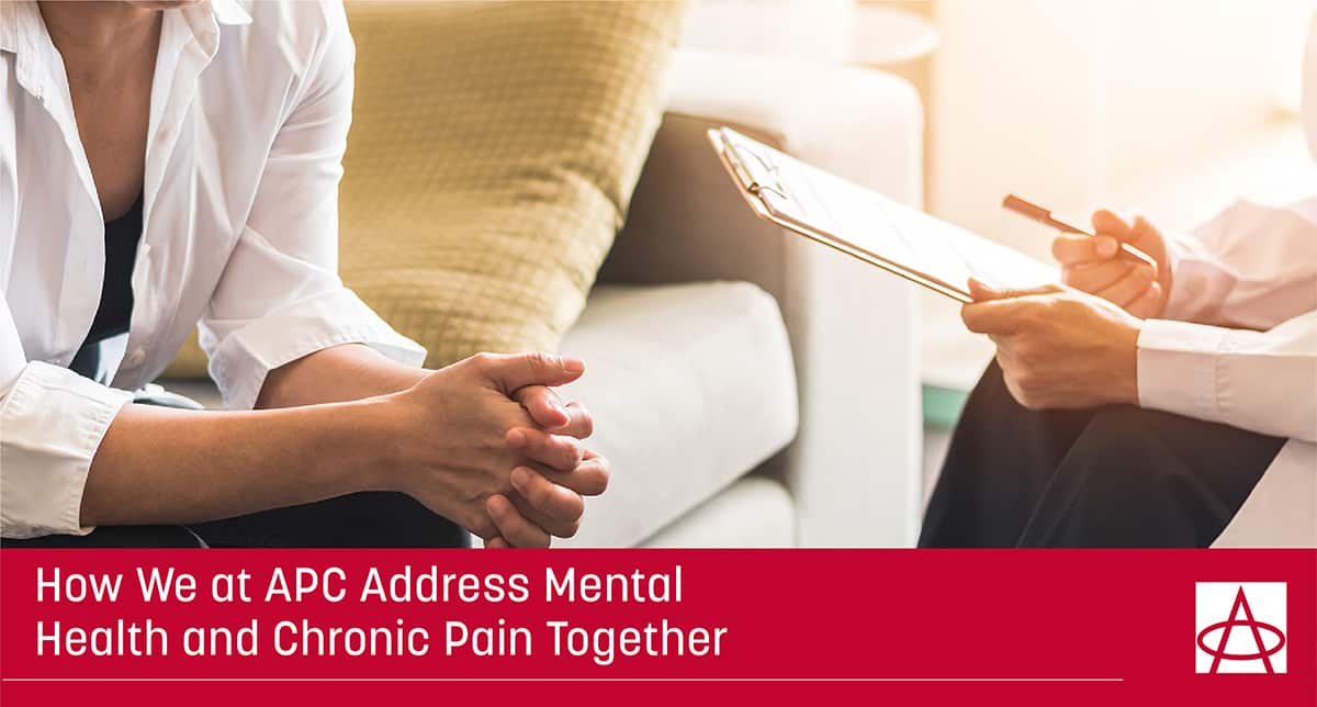header image for blog A woman sits forward with her hands clasped together on a couch accross from a doctor with a clipboard the caption says How We at APC Address Mental Health and Chronic Pain Together