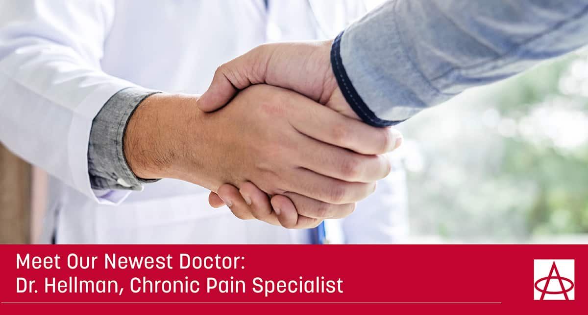 header image for the blog a doctor in a white coat is shaking hands with a man in a grey long sleeve shirt the caption reads meet our newest doctor dr. hellman chronic pain specialist