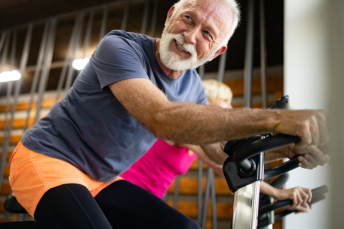 Mature Fit People Biking In The Gym, Exercising Legs Doing