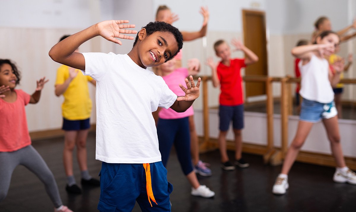 Portrait,Of,Smiling,African,Boy,Showing,Dance,Elements,During,Group