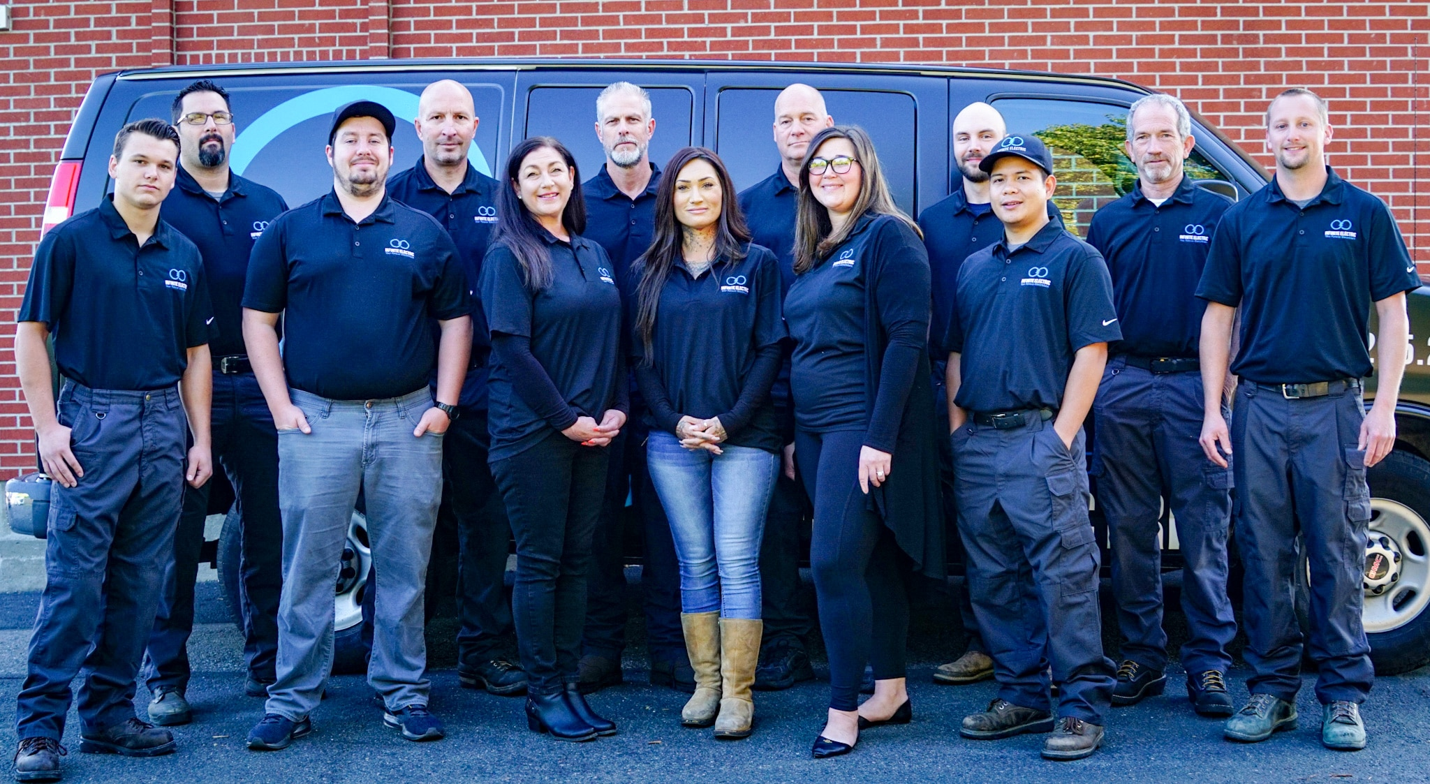 The full team of electricians at Infinite Electric standing in front of a service van.