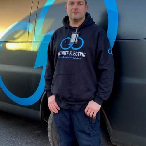Infinite Electrician Nick standing by his service van