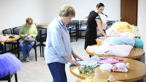 Anna Curtis (back) teamed up with several artists in Chilton County including Sue Anne Hoyt (front) and Diana Hiott, who helped in costume preparations.