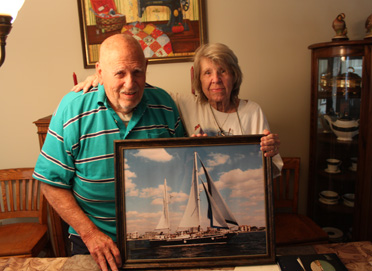 """Clanton's Henry Edward Moore and wife, Joan, hold a picture of their boat """"Sweet Talk"""" which the couple built years ago. Now, the couple spends time looking over stacks of photo albums and ship logs to remember their travels on the boat."""