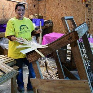 Julie Lada holds a finished mat that will be shaped into a basket. (Joyanna Love/Advertiser)