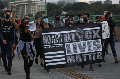 A group of people marching across Key Bridge in Washington D.C. during a BLM Protest