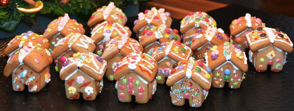 Rows of mini, brightly decorated gingerbread houses sit in front of a holiday Christmas tree. The cookies are decorated with colorful candies and sprinkles with icing and frosting.