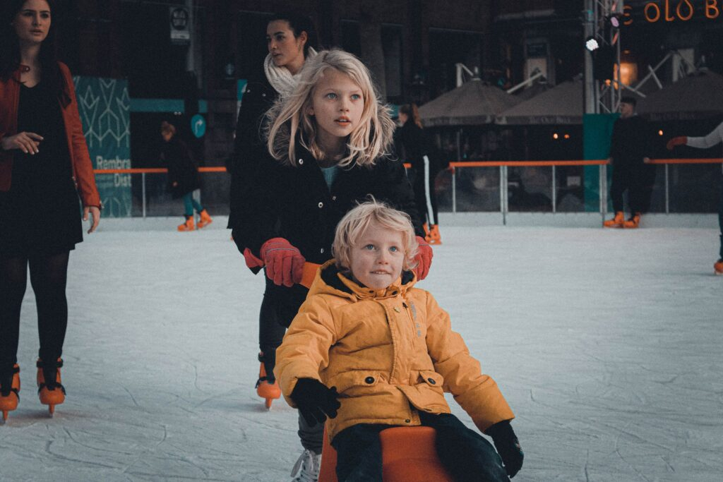 Two children are on an ice skating rink. The older sister is pushing her younger brother on a scooter.