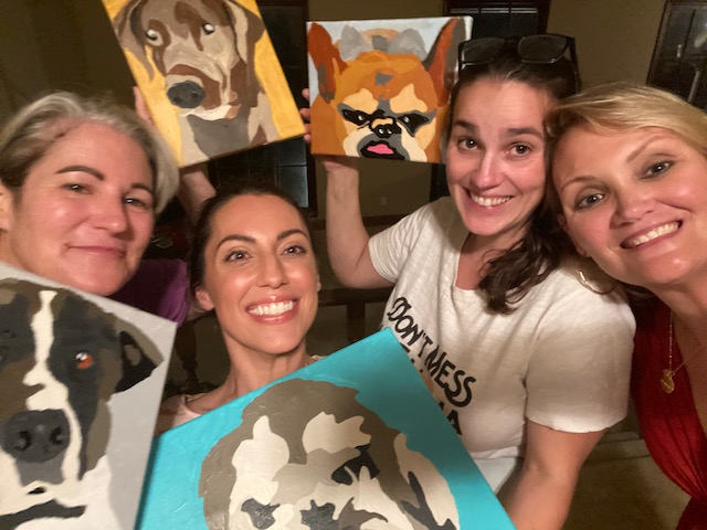 Mom and daughter painting their pet portraits together smiling and happy.