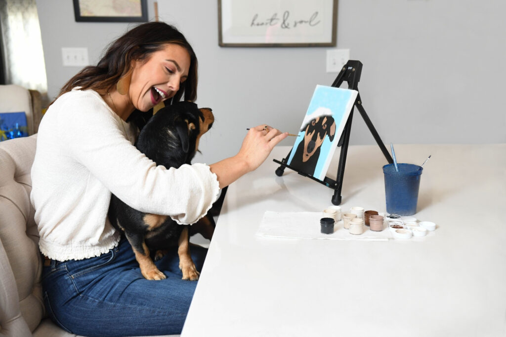 smiling happy woman with dog on lap while painting canvas of her dog