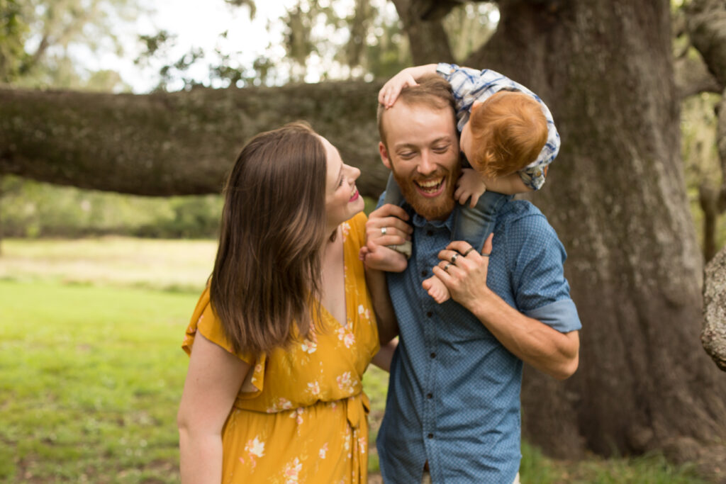 Couple with their one year old playing peek-a-boo
