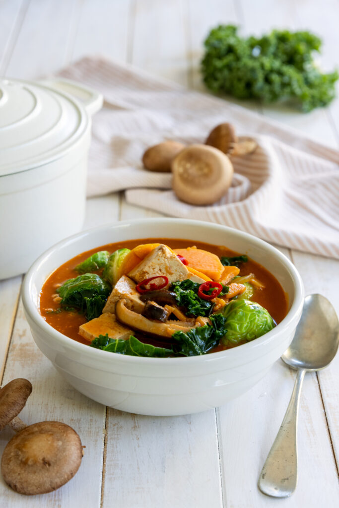 Fall Sweet Potato Kale Coconut Curry Soup in a white bowl with a spoon
