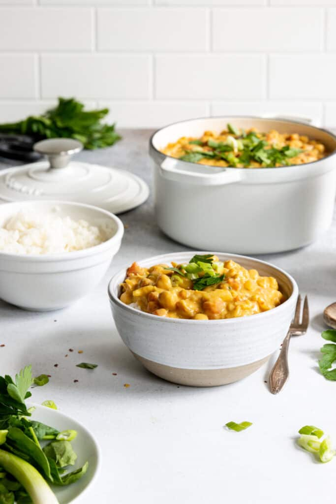 Chickpea Coconut Curry served in a white bowl with fresh herbs