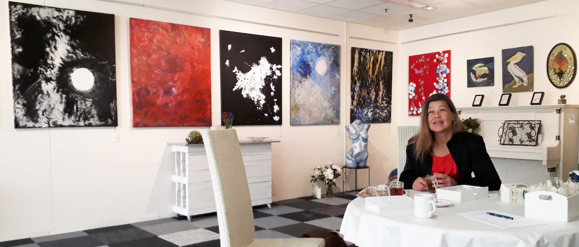 Artist Laura Meddens sits at a round white table with a cup of tea with some of her paintings hanging on the walls in the background at Galerie The Window in Zuidland in the Netherlands.