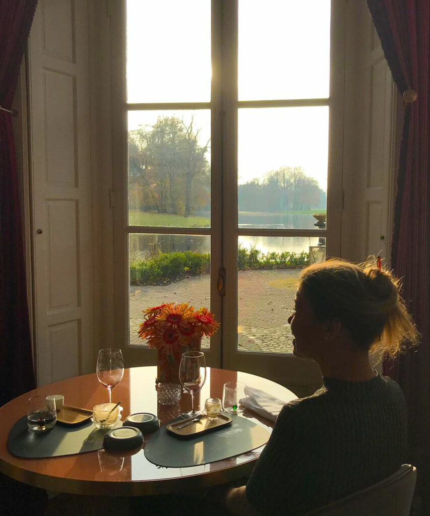 Blind painter Laura Meddens sits at a round table in Restaurant Voltaire with a view of the pond where she skated as a child in the winter.