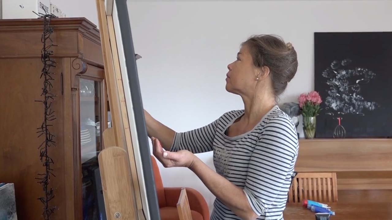 """The Artist. Photo of Laura Meddens working at her easel while the painting """"Tango"""" sits on top of a piano in the background."""