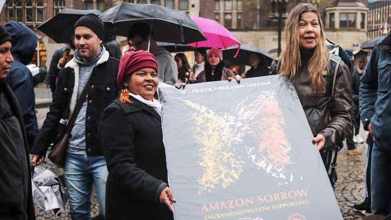 Amazon Sorrow banner. Photo of Laura Meddens presenting a poster of her painting Amazon Sorrow to indigenous leaders from the Amazon at a demonstration in Amsterdam's Dam Square.