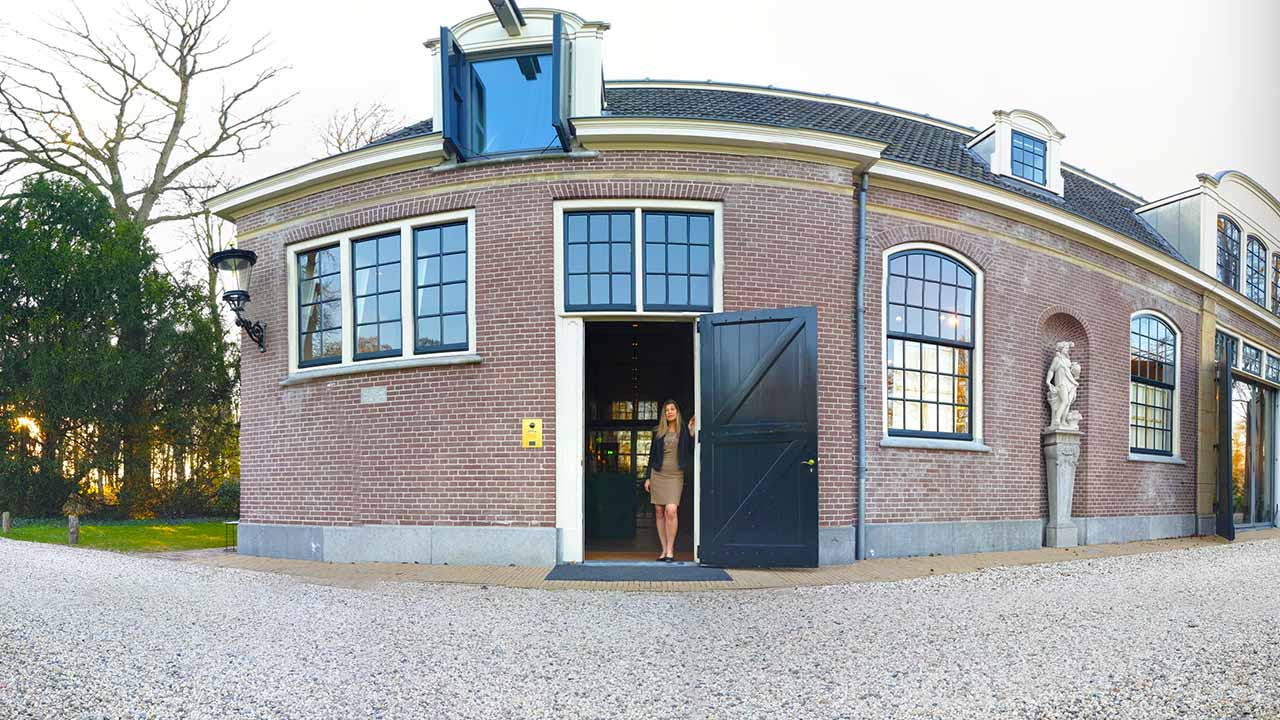 Blog banner. Photo of Laura Meddens standing in a doorway of the Carriage House where her solo exhibition was held on the estate of Parc Broekhuizen in The Netherlands.