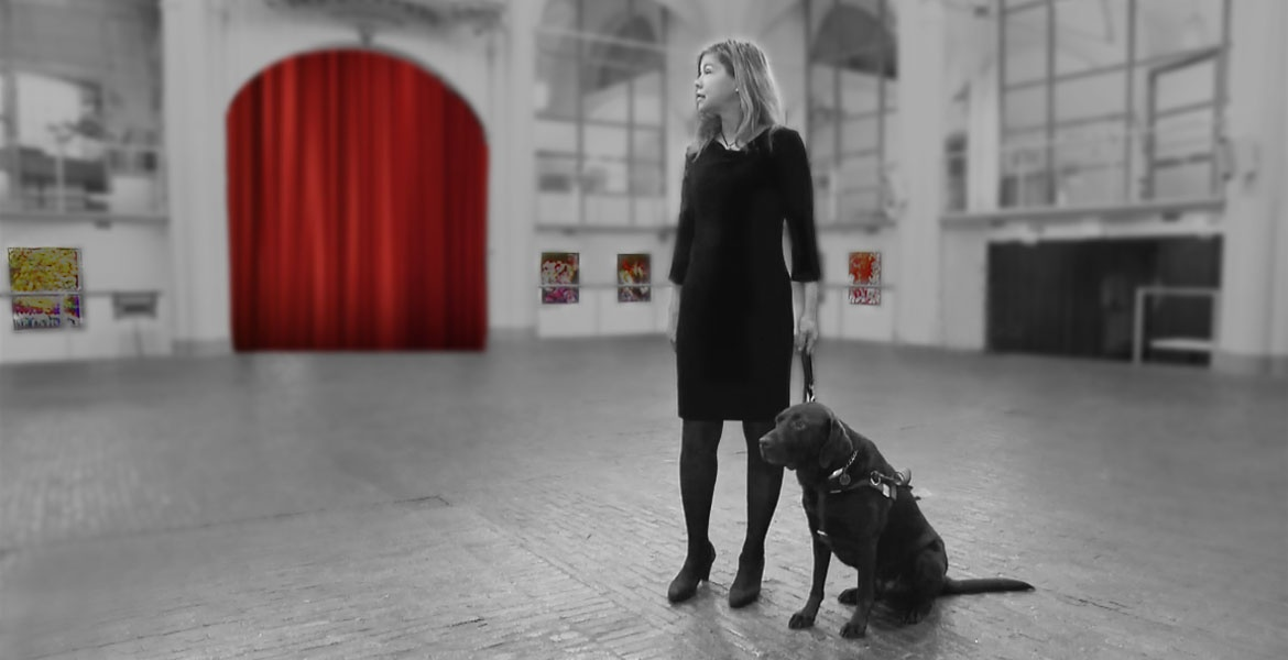 Exhibitions banner. Photo of Laura Meddens and her Seeing Eye guide dog Nugget stand in the middle of her solo exhibition in the historic Amstelkerk in Amsterdam.