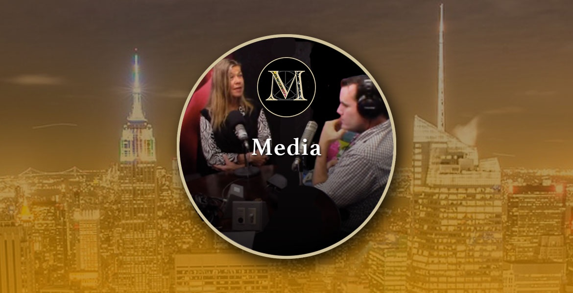 Media. Photo of Laura Meddens being interviewed by Mark Farrell in New York City inside the gold ring icon logo with a nighttime cityscape of New York in the background.