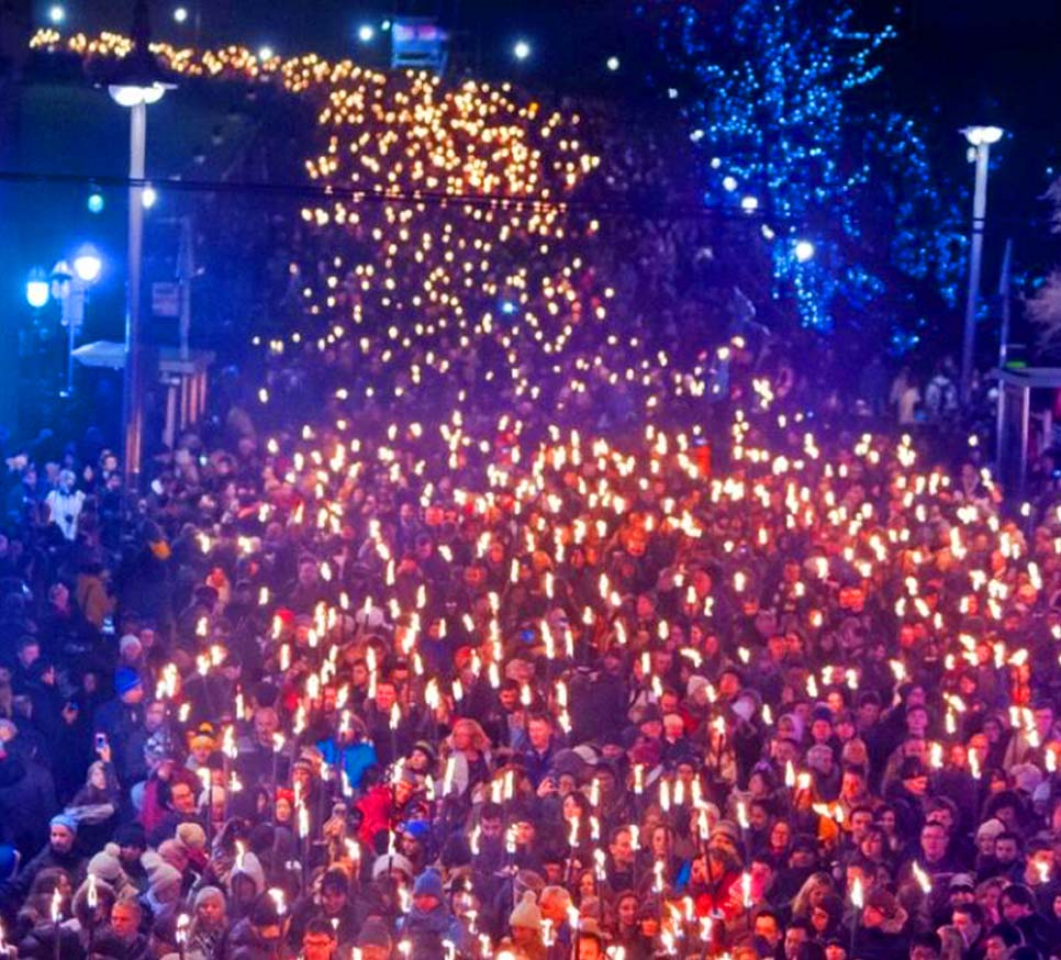 """A photo of Edinburgh's Hogmanay torchlight parade resembles the imagery in Laura Meddens' painting """"Celebration""""."""