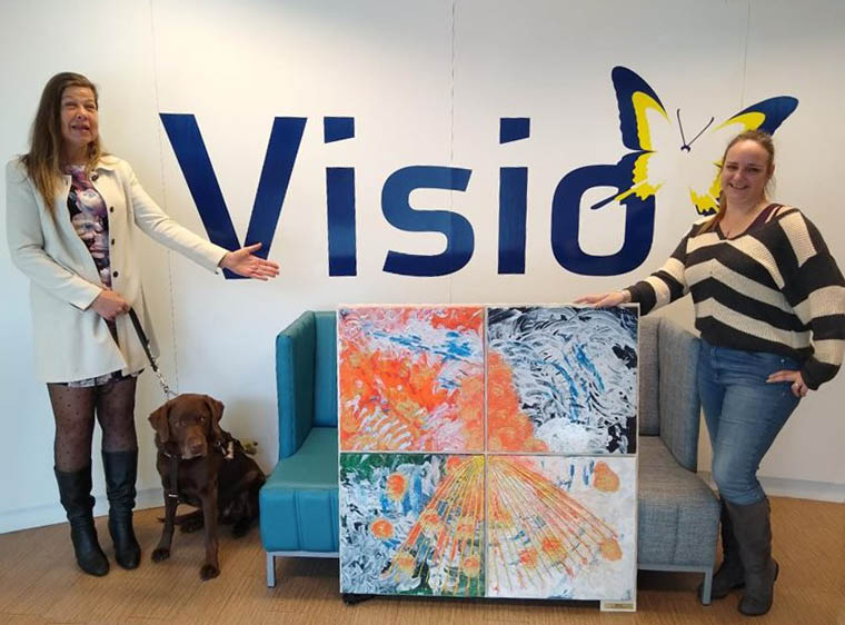 """Laura Meddens stands with her Seeing-Eye guide dog Nugget as she presents a print of """"Seasons"""" to Visio's occupational therapist Hubertine Kramer - Burgers."""