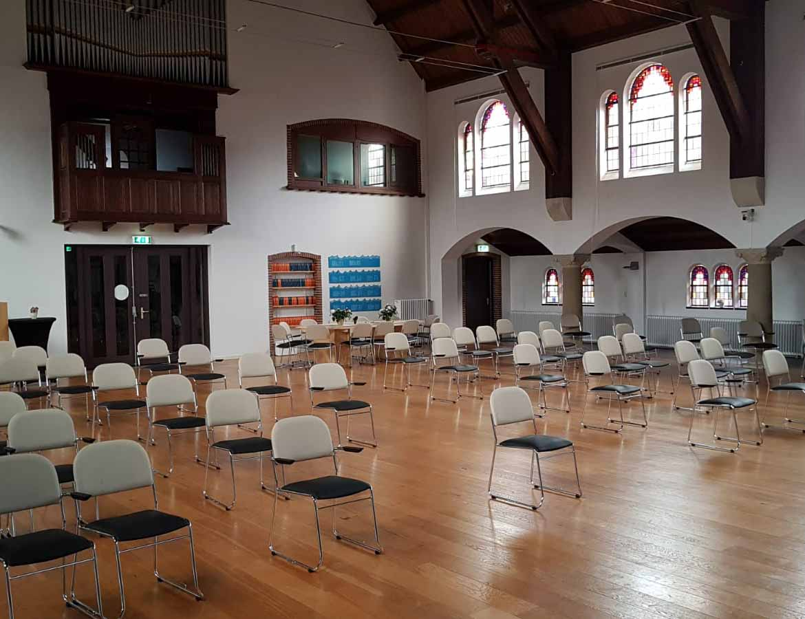 A photo of the main hall at Verhalenhuise Haarlem showing chairs placed in a socially-distanced way.
