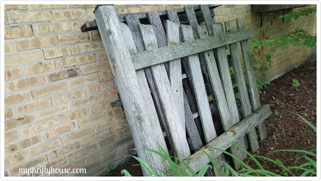 Old fence and pallets used to make an outdoor dartboard.