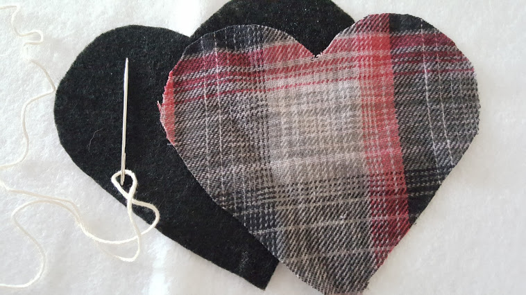Sewing the plaid flannel puffy heart Valentines with some embroidery thread.