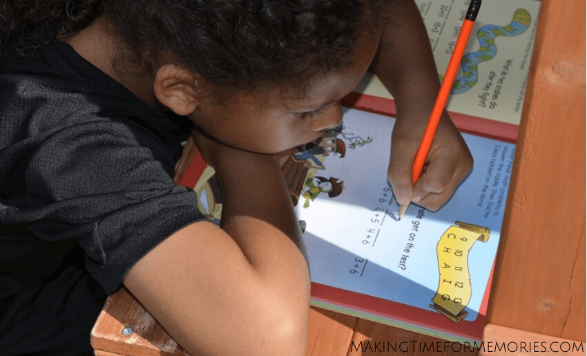 1st grader practicing math in a Highlights learning book