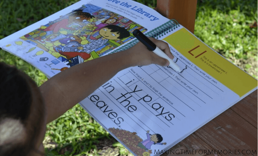 preschooler learning to trace letters in a Highlights learning book