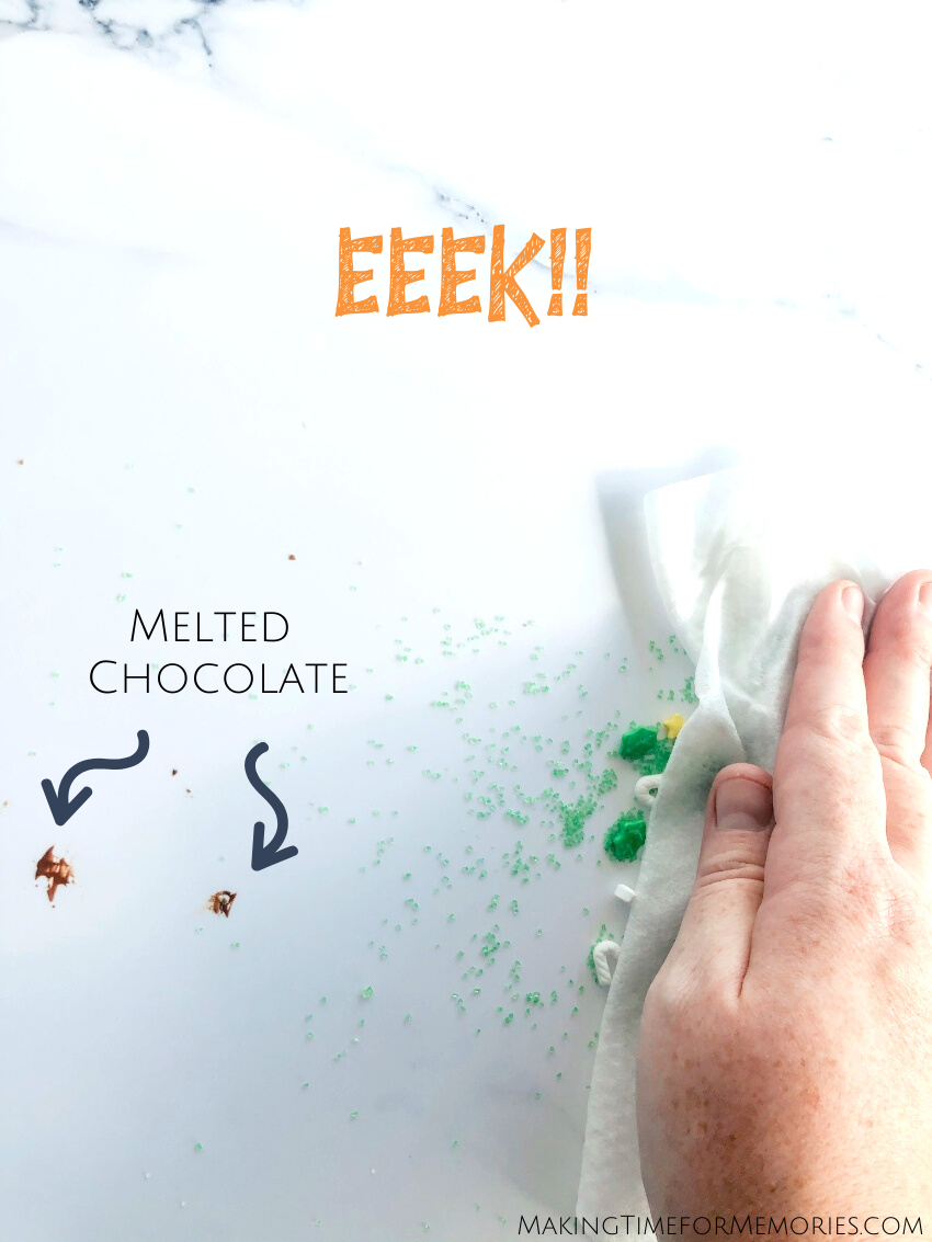 wiping melted chocolate and sprinkles off of a SnapIt Boards backdrop