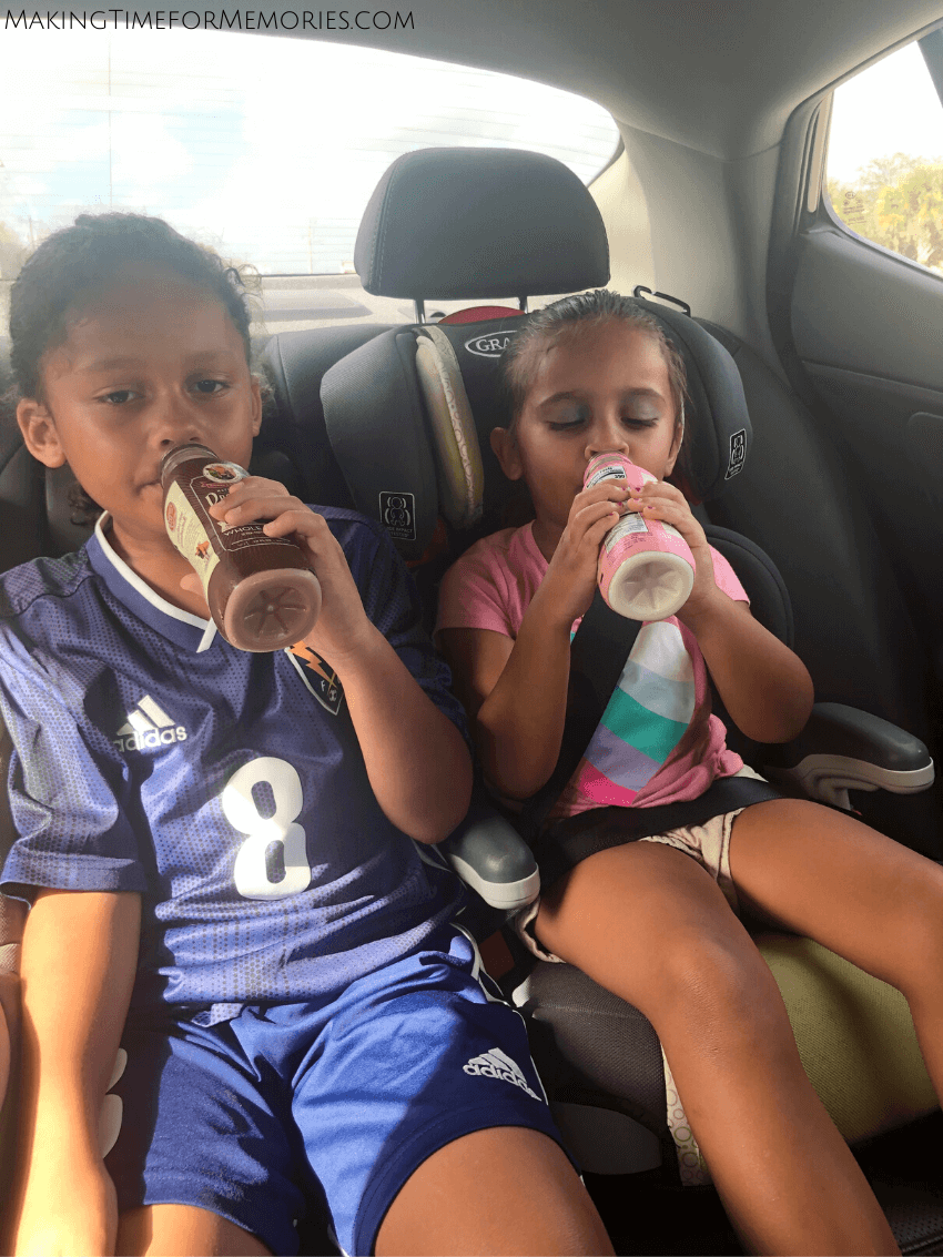 little boy and little girl in the back seat of a car, drinking chocolate and strawberry whole milk, while on the way to a soccer game