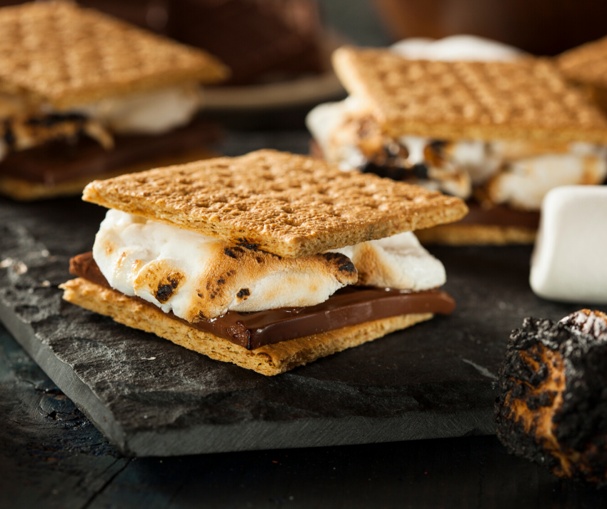 """Buzz Lightyear's """"Hot Delicious Schmoes"""" (S'mores) - a piece of chocolate and a melted marshmallow between 2 graham crackers"""