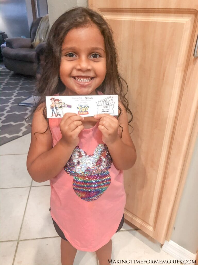 little girl holding her Toy Story movie night ticket