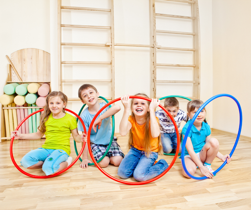 5 kids smiling and holding their hula hoops