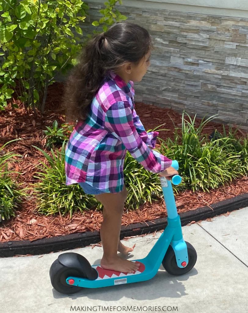4 year old girl riding a Razor Wild Ones Junior Kick Scooter on the sidewalk
