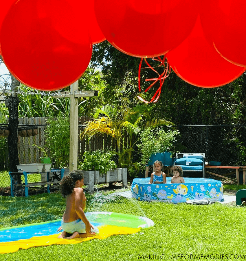kids cooling off in kiddy pool and slip 'n slide