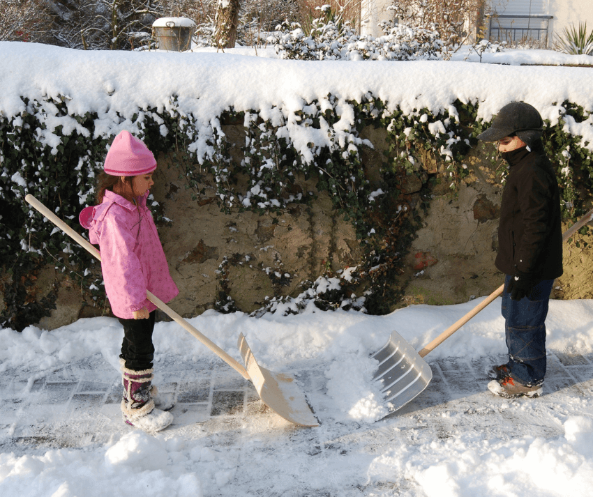 2 kids participating in the snow shoveling event for the Family Holiday Olympics