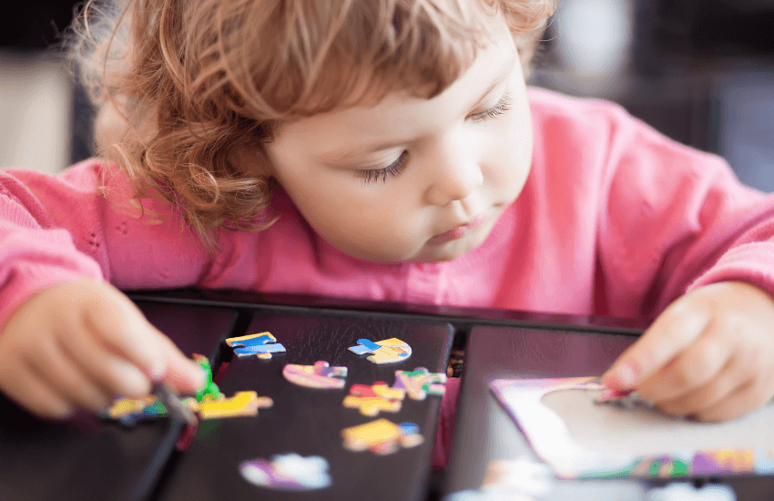 toddler/preschool aged girl putting together a jigsaw puzzle