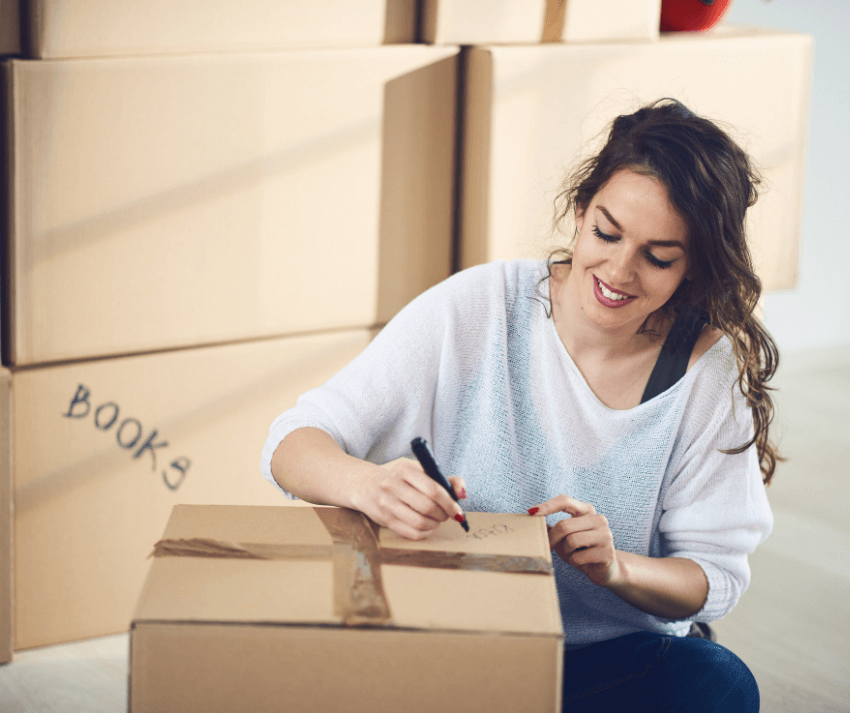 woman packing to move and labeling boxes