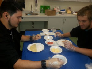 Two students working with pizza ingredients