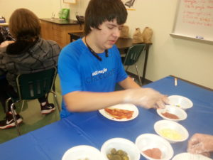 Student working with pizza ingredients