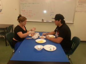 Two participants making pizza