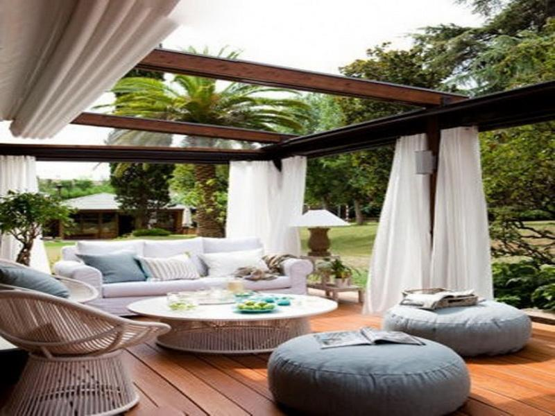 modern-classic-home-exterior-design-ideas-on-sustainable-teak-parquet-deck-and-wide-pergola-along-with-white-sheer-vertical-curtain-as-cover